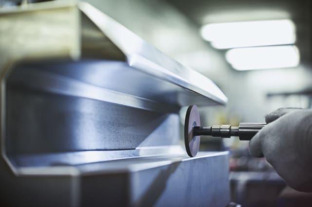 Close up worker sanding steel in steel factory