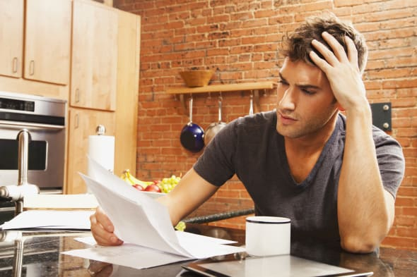 Caucasian man looking at paperwork in kitchen