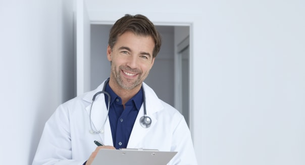 Doctor In His Office Holding A Clipboard