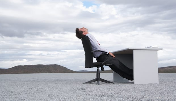 Man sitting at a desk outdoors with his head back