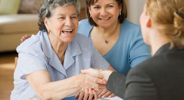 Senior Hispanic woman shaking hands with businesswoman