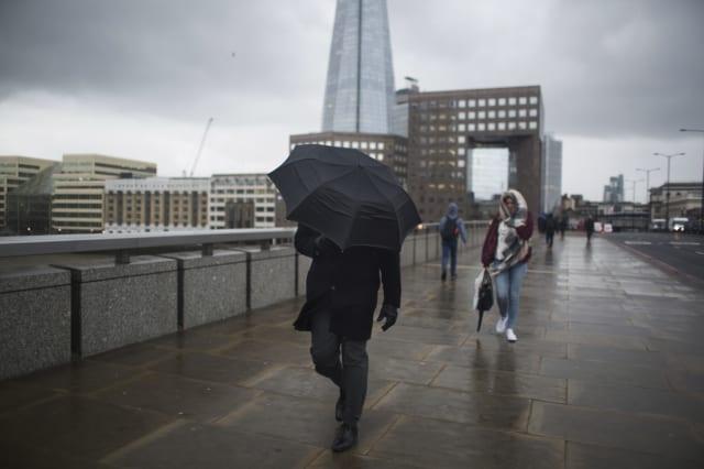 Crossing London Bridge Struggling With An Umbrella