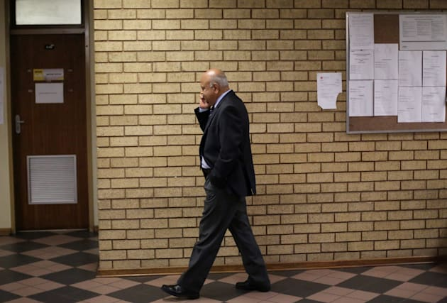 South Africa's Finance Minister Pravin Gordhan speaks on his mobile outside a court room in Pretoria,...