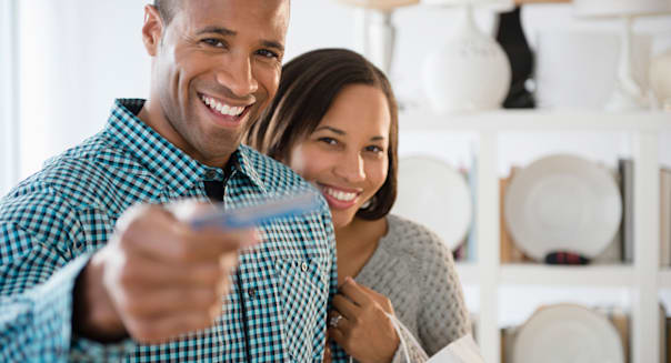 Portrait of happy couple paying with credit card in store