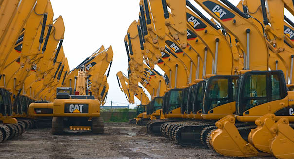 caterpillar excavator neatly parked in open yard storage in repetitive pattern