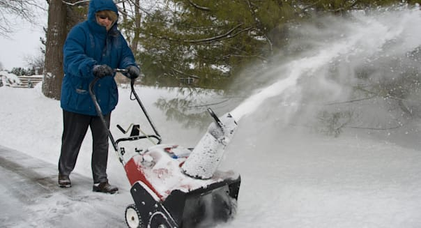 Woman clearing snow with a snow thrower
