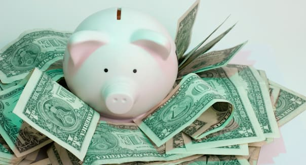 A Pink Piggy Bank Surrounded by US Dollars against a white background