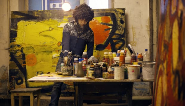 Young male artist amongst paintings and brushes
