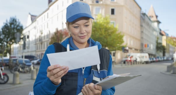 Female postal worker looking through mail