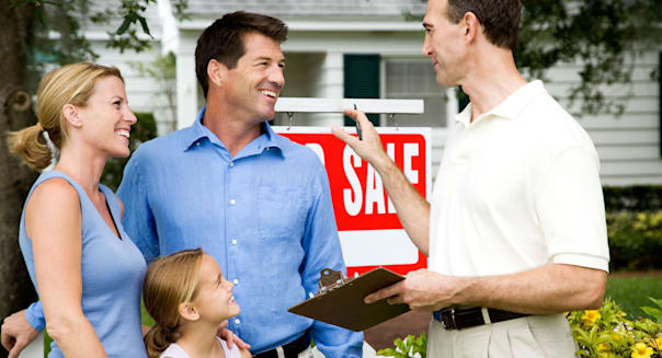 Family with estate agent outside property for sale
