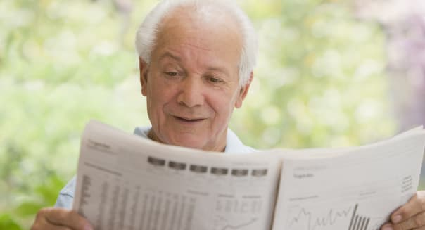 Senior Hispanic man reading financial newspaper