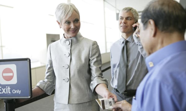 Mature businesswoman showing agent ticket at airport