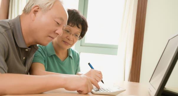 Side profile of a mature couple using a calculator