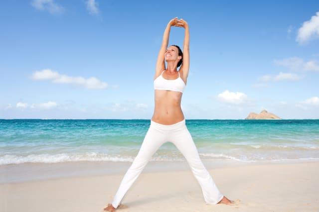 Smiling healthy woman practicing yoga on Lanikai Beach, Oahu, Hawaii.