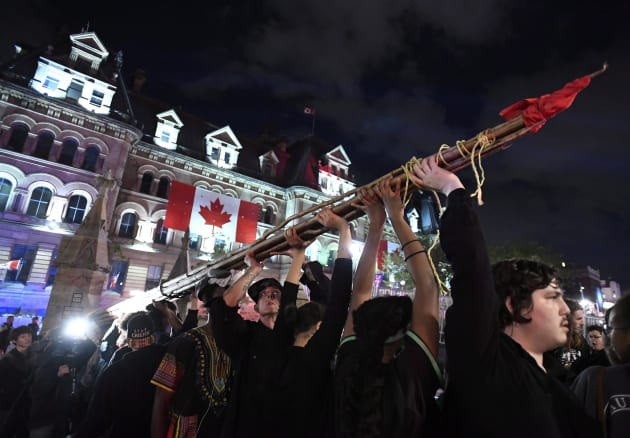 People hold a teepee, intended to be erected on Parliament Hill as part of a four-day Canada Day protest...
