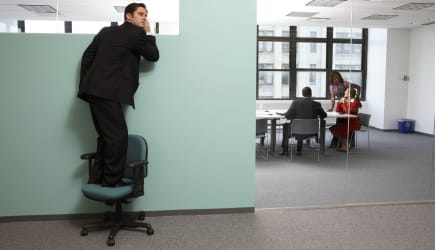 Businessman standing on chair listening to office meeting