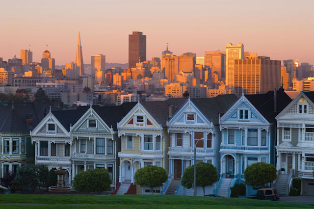 ANXTXJ Victorian houses on Alamo Square with the city skyline in the background, San Francisco, California, USA.