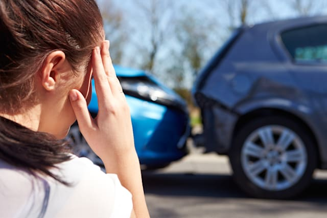 Stressed Driver Sitting At Roadside After Traffic Accident looking at the damage