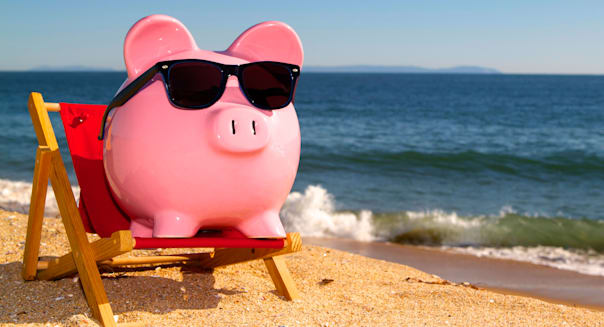 Pink piggy bank on a beach in a deck chair wearing sunglasses with golden sand a blue ocean and vivid blue sky