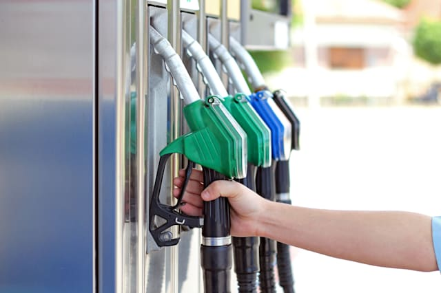 Close-up of a men's hand using a fuel nozzle at a gas station.Petrol station. Filling station. Petrol. Gasoline.