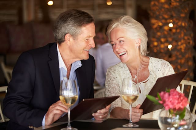 Senior Couple Choosing From Menu In Restaurant