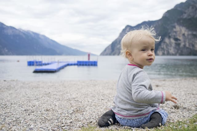 Baby playing on rocky beach