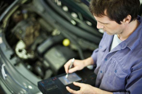 BM8XYM Mechanic using electronic tools to evaluate car performance