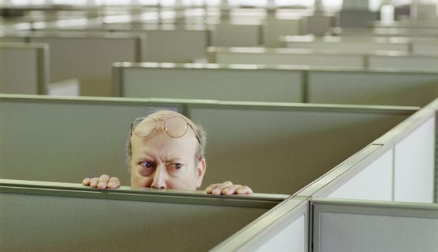 Older man hiding behind office cubicle