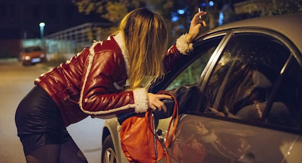 Prostitution in a city - night prostitute talking to potential customer