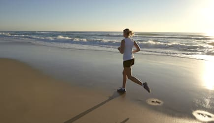 Young woman running on beach.