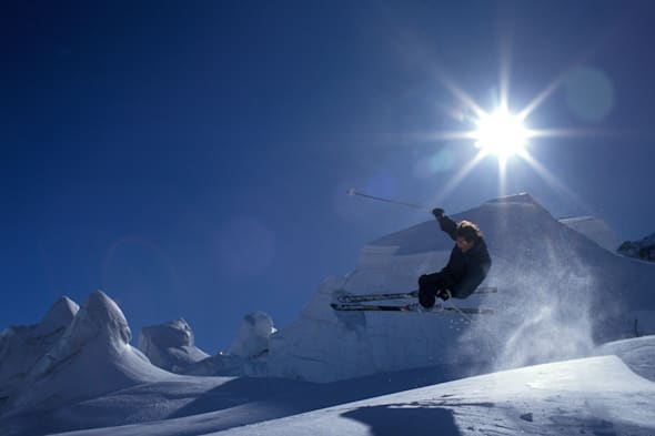 Dramatic image of an extreme lone skier off piste in mid air in the snowfields high above Chamonix in the French Alps