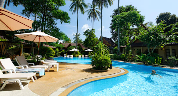 Bungalow resort with green surroundings and pool, sun chairs, high palm trees, swimming woman, Palm Garden Resort, Phuket City,
