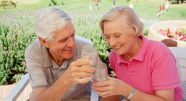 Outdoor portrait of retired couple enjoying a drink at the golf club.