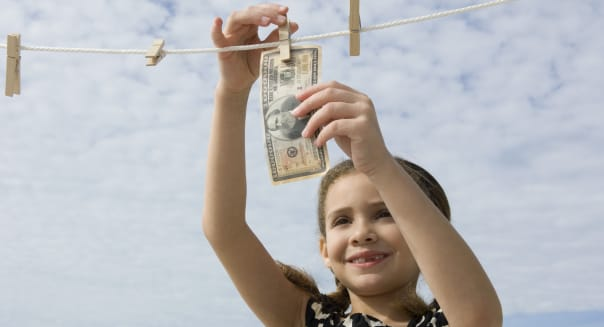 Girl hanging one million dollar bill on clothes-line