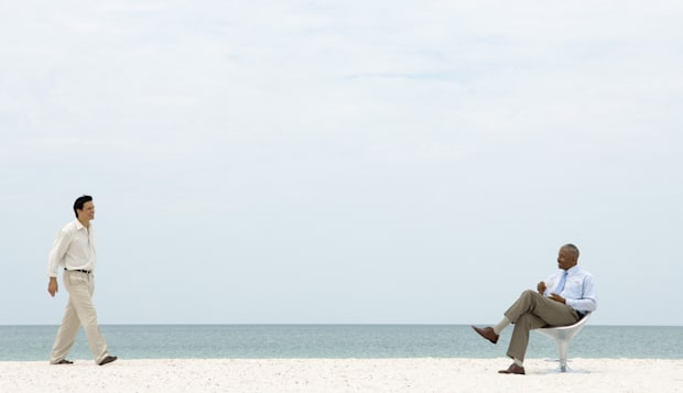 Businessman at the beach walking toward seated colleague, both smiling