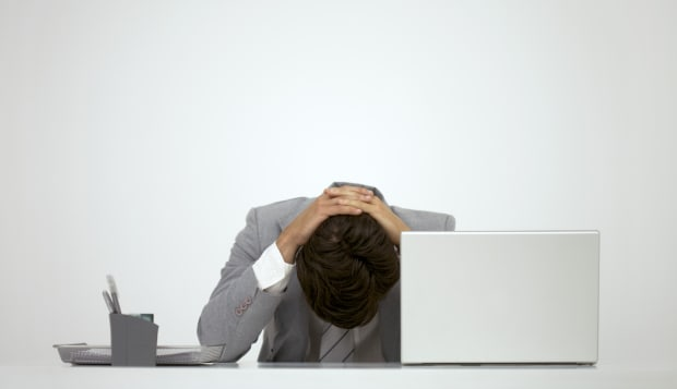 Businessman sitting at desk with head down