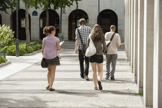 University students walking on campus, rear view