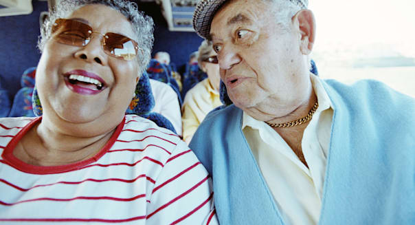 Mature couple on tour bus, smiling