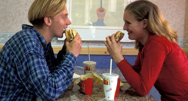 Teenage couple sitting at table in fast food outlet eating burger and french fries