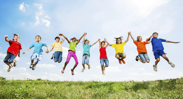Happy kids with raised arms jumping in the nature against the sky.