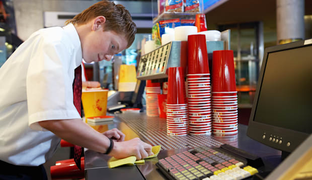 Teenage boy (14-16) cleaning refreshments counter in cinema