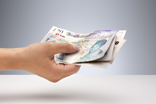 Hand holding English currency
