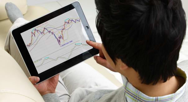 Man looking stock market on digital tablet