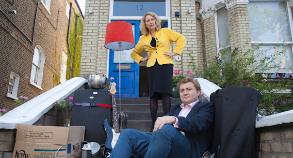 Boomerang Generation: a young man in his twenties sits on his parents doorstep having moved back home after graduating, UK