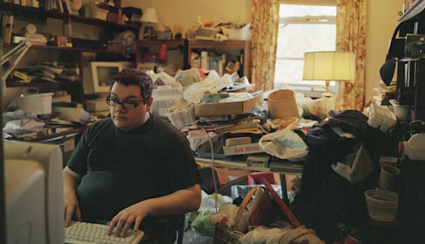 Young man using computer in messy room