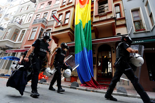 Riot police, with a rainbow flag in the background, chase LGBT rights activists as they try to gather...