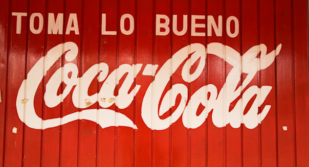 MEXICO Todos Santos Advertising for Coca Cola in Spanish painted on side of red wooden building Toma lo Bueno slogan