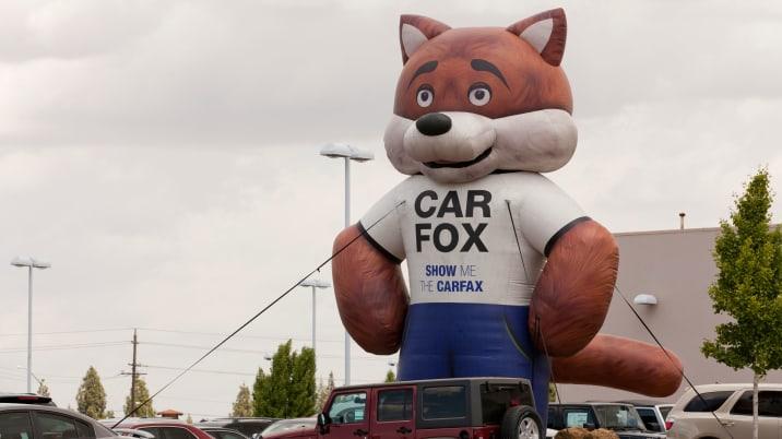 Carfax Carfox balloon display at a used car sales lot - California USA