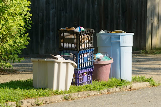 Bins of comingled recycling wait on curbside for pickup.