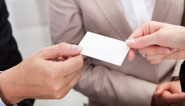businesspeople exchanging cards ...